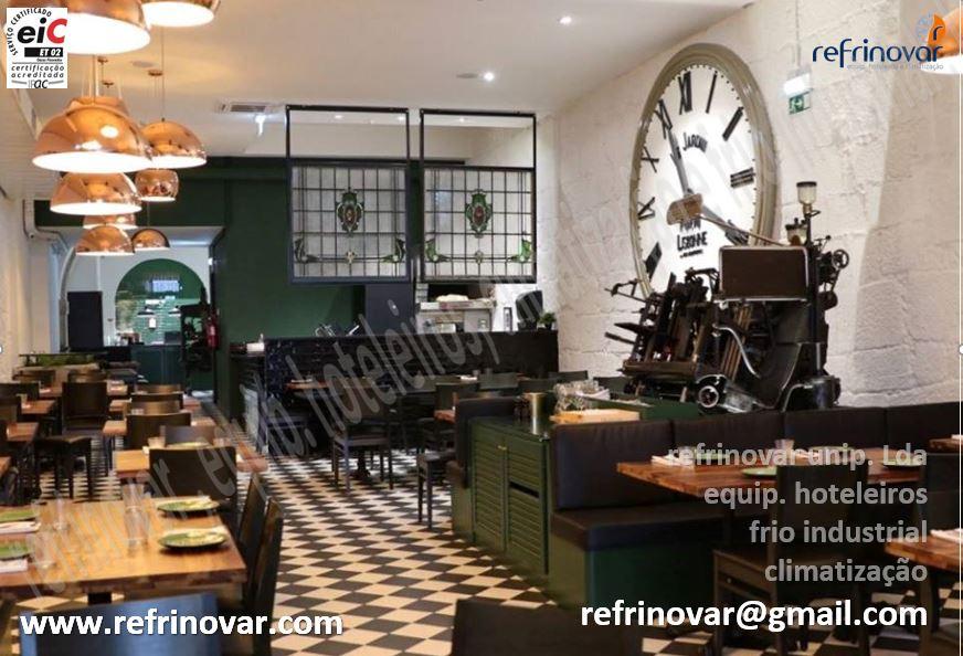 Espaço equipado pela Refrinovar, incluindo ar condicionado e ventilação, com uma zona de padaria, zona de bar, zona de cozinha e copa ao fundo da sala.