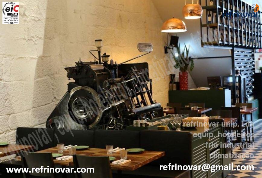 Máquina de tipografria antiga, com mini-balcão na retaguarda, garrafeira de vinho, e vitrina de queijos refrigerada personalizada.