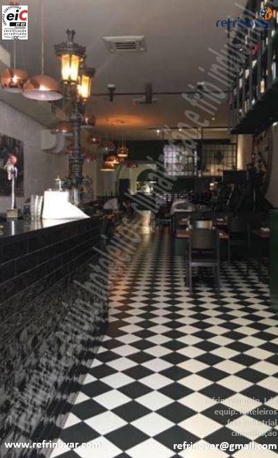 Vista em profundidade da sala de jantar com o balcão de bar da entrada equipado com móveis e máquinas da Refrinovar.