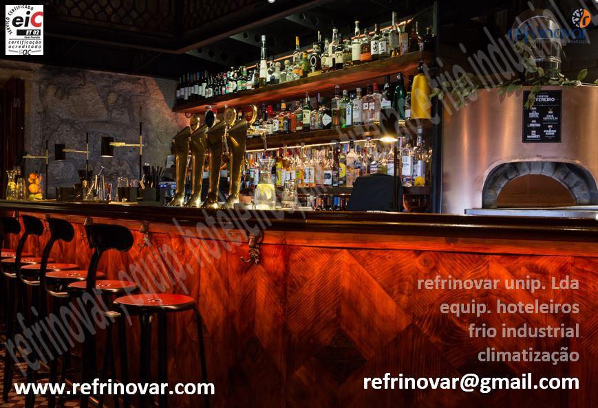 Balcão alto rústico, com bancos altos, forno de pizzas italiano a gás enquadrado no meio da zona de bar.