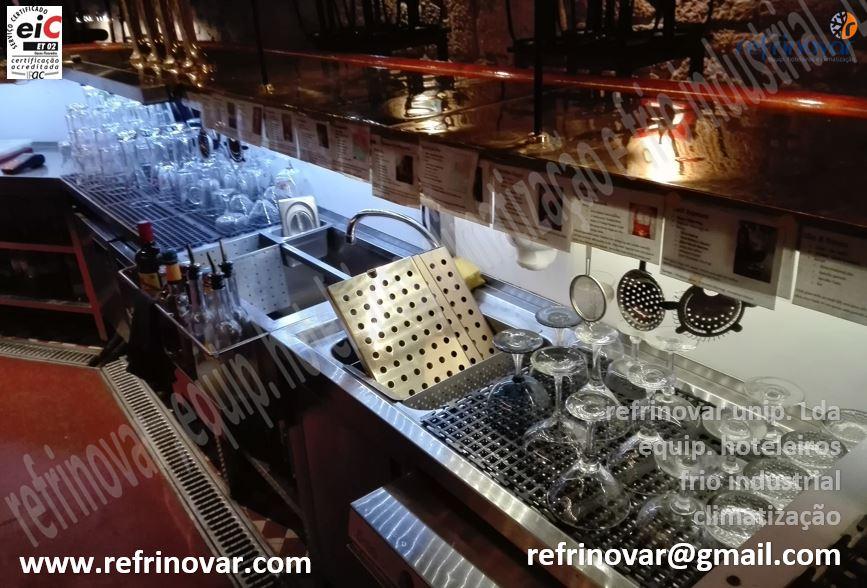 Bancadas inox neutras, estilo bar inglês, com zona de recepção de gelo, encaixe de garrafas, escorredouro para copos etc.