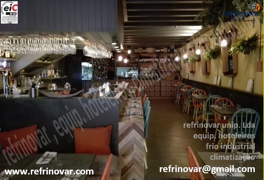 Aspecto exterior do balcão do bar e da sala interior, com a cozinha ao fundo resguardada pelo móvel